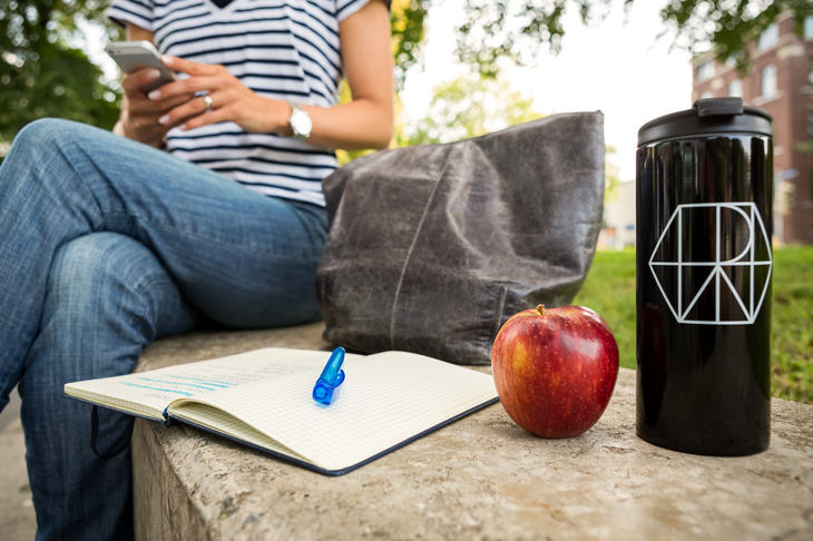 Female student sitting on a wall with an open book, apple, and thermos next to her