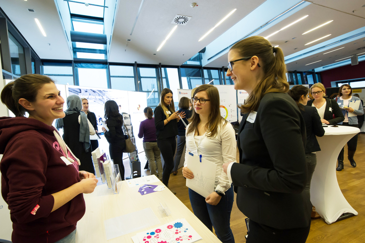 Women standing at a table at an info fair